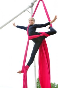 Active smiling sportive cheerful child training dancing performing and on aerial silks or ribbons. Childhood, sports, happiness, active lifestyle concept.